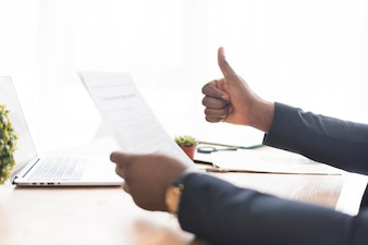 Businessman with paper gesturing thumb up