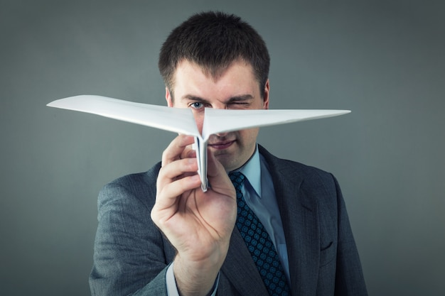 Бизнесмен с бумажным самолетиком в студии