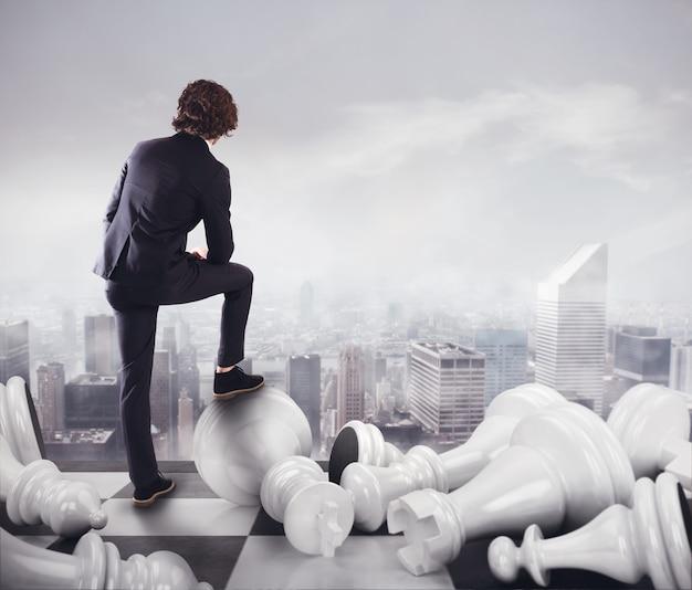 Бизнесмен с пешками в шахматы наблюдает за городской пейзаж
