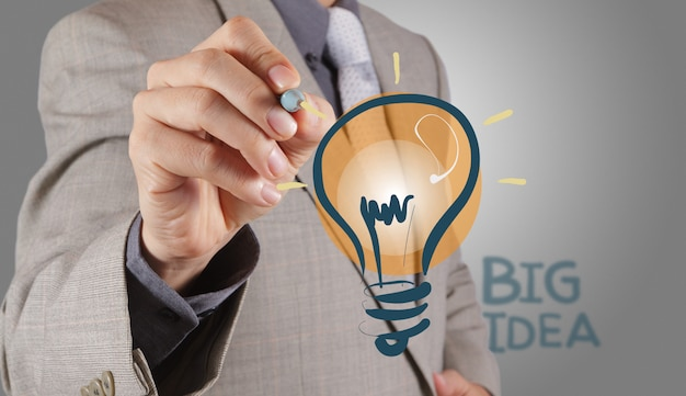 Businessman with a pen drawing light bulb