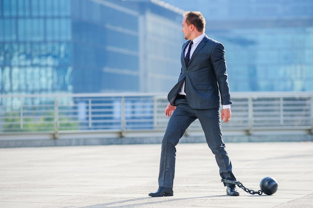 足に囚人のボールを持つビジネスマン。
