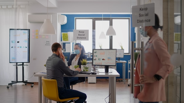 ビジネスミーティングを組織する電話で話している保護フェイスマスクを持つビジネスマン。コロナウイルスの世界的大流行の際に会社のオフィスで働いている間、社会的距離を尊重する同僚