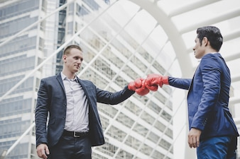 Businessman with red boxing gloves ready to fight his coworker.