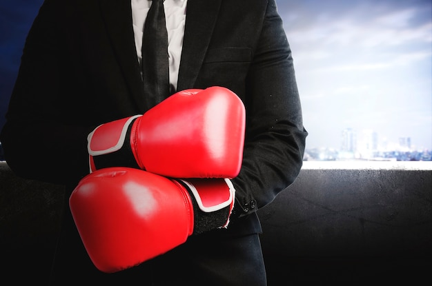 Businessman with red boxing gloves with cityscapes background