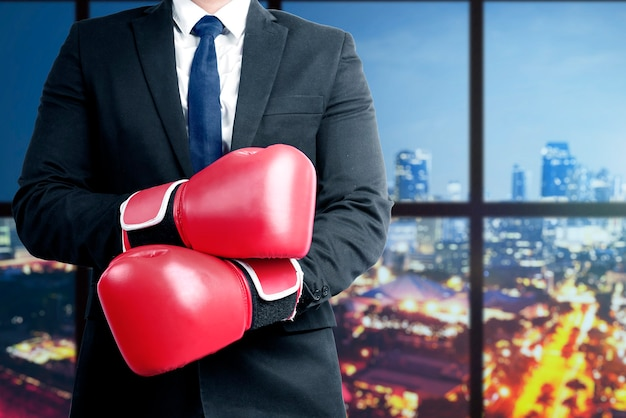 Businessman with red boxing gloves with office building