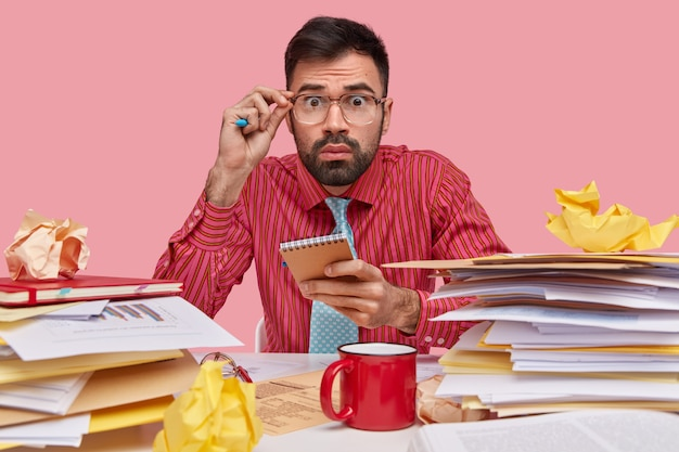 Businessman with scared expression feels frustrated, has finance sheets on desk, holds notepad, drinks coffee, wears formal shirt