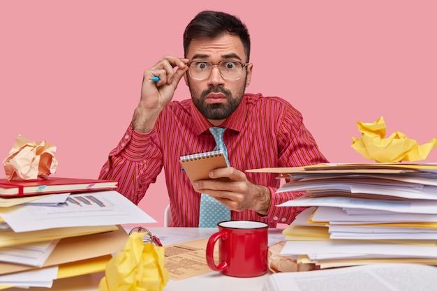 무서워하는 표정의 사업가는 좌절감을 느끼고 책상에 재무 시트를 가지고 있으며 메모장을 들고 커피를 마시고 공식 셔츠를 입습니다.
