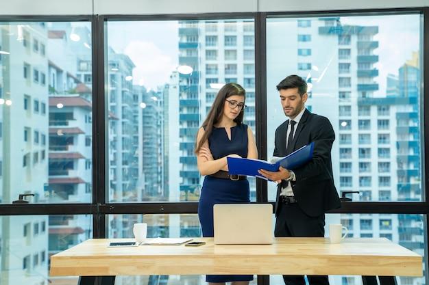 Бизнесмен с секретарем, работающим и общающимся в современном офисе, мужчина и женщина обсуждают работу вместе.