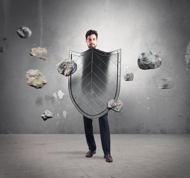 Бизнесмен с щитами. концепция защиты и защиты в деловом мире