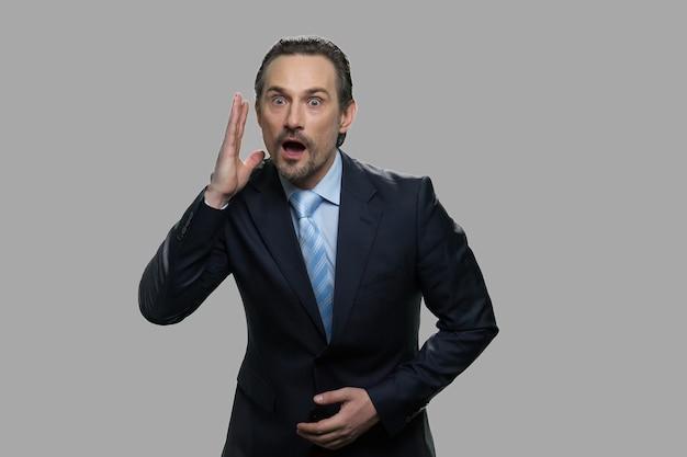 ショックを受けた表情を持つビジネスマン。灰色の背景に対して驚いた怖いビジネスマン。