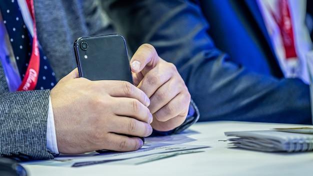Бизнесмен с смартфоном на торговой ярмарке