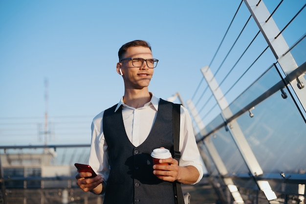 Businessman with a smartphone drinks coffee on the office terrac