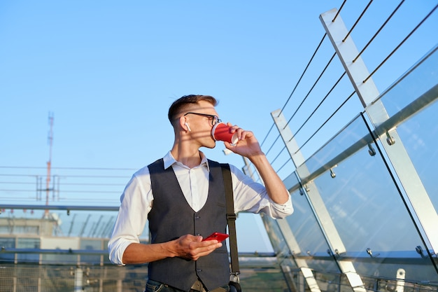Businessman with a smartphone drinks coffee on the office terrace . close-up.
