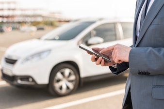 Businessman with smartphone in front of car