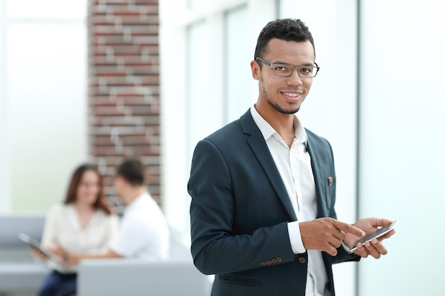 現代のオフィスに立っているスマートフォンを持つビジネスマン。