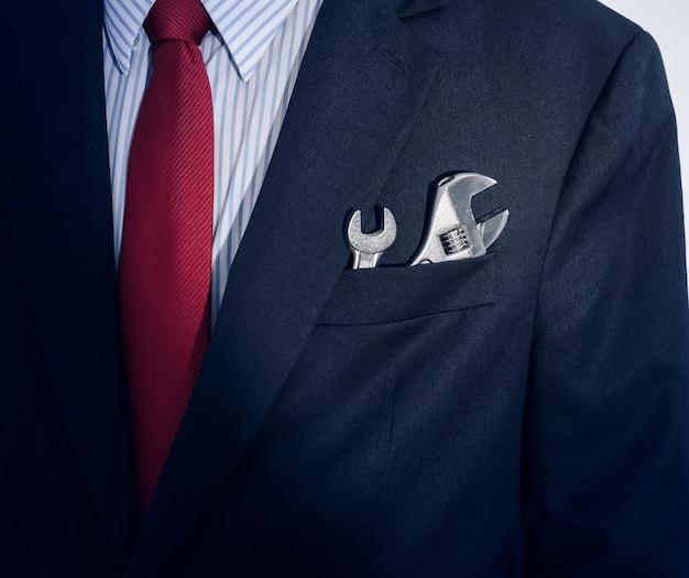 Бизнесмен с гаечным ключом в кармане костюма