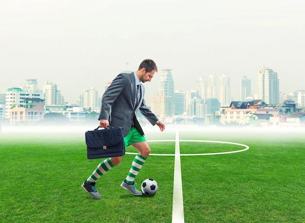 Бизнесмен с чемоданом в спортивной одежде играет в футбол на городском стадионе