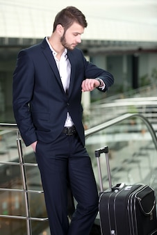 Businessman with a suitcase looking at the wrist watch