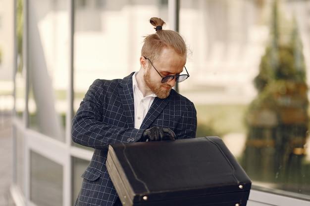 夏の街を歩いてスーツケースを持ったビジネスマン
