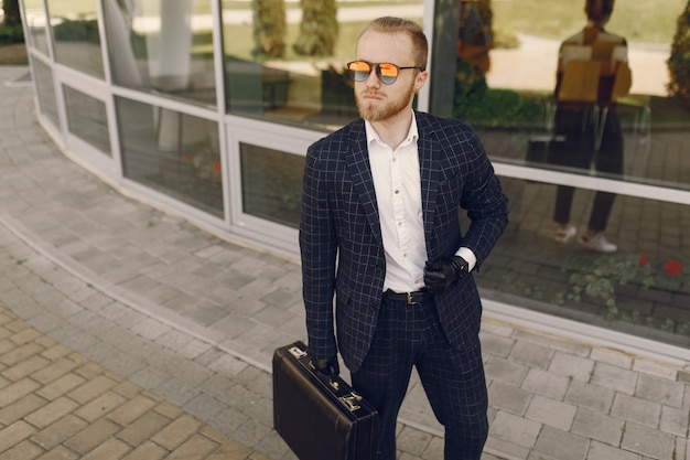 Businessman with suitcase walking in a summer city