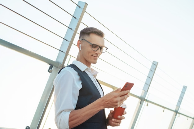 Businessman with a takeaway coffee using his smartphone on the o