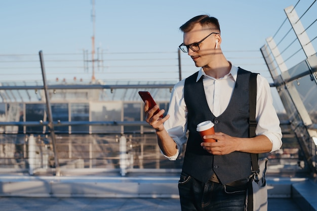 Businessman with a takeaway coffee using his smartphone on the office terrace . people and technologies.