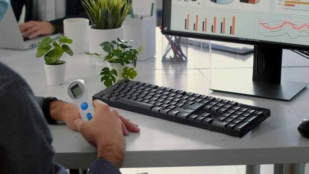 Businessman with thermometer start working on computer while sitting at business company office during virus infection. coworkers with face masks keeping social distancing