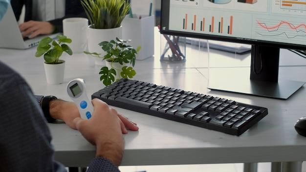 温度計を持つビジネスマンは、ウイルス感染中に事業会社のオフィスに座っている間、コンピューターで作業を開始します。社会的距離を保つフェイスマスクを持った同僚