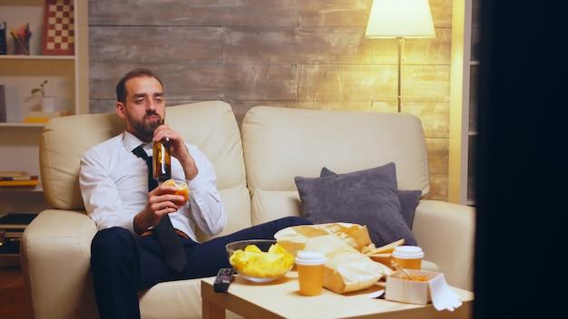 Бизнесмен с галстуком, сидя на диване, ест гамбургер и разговаривает по телефону.