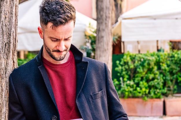 잘린 된 수염과 사업가입니다. 긴 검은 색 코트를 입는다. 그의 휴대 전화를 사용합니다.