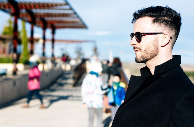 도시 공간에서 잘린 된 수염을 가진 사업가. 긴 검은 코트와 선글라스로 옷을 입으십시오.