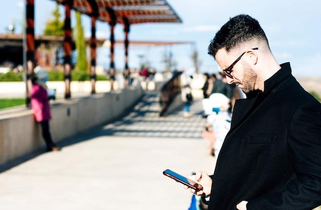 도시 공간에서 자신의 휴대 전화를 사용하여 잘린 수염을 가진 사업가. 긴 검은 코트와 선글라스로 옷을 입으십시오.