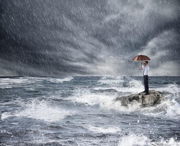 Бизнесмен с зонтиком во время шторма в море