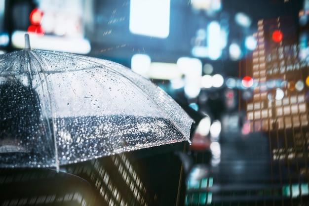 Uomo d'affari con l'ombrello in città piovosa