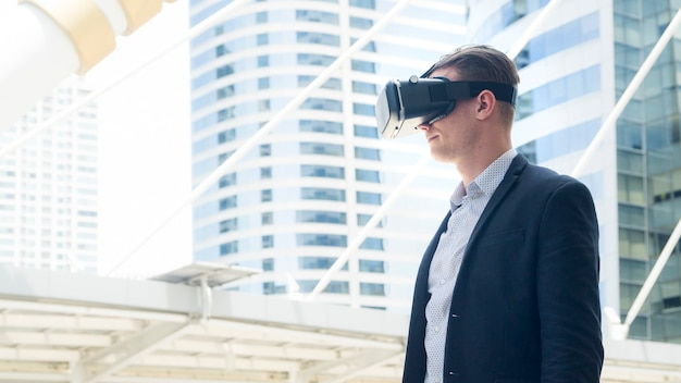 Businessman with vr glass for smartphone stand at outdoor.