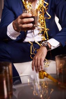 Uomo d'affari con whisky al night club
