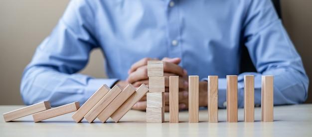 木製のブロックまたはドミノを持ったビジネスマン。ビジネス