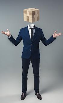 회색 스튜디오 배경에 머리 대신 나무 게임 상자를 가진 사업가입니다.