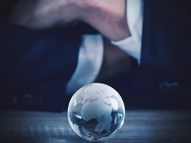 テーブルの上に大陸を持つ世界のガラス球を持つビジネスマン