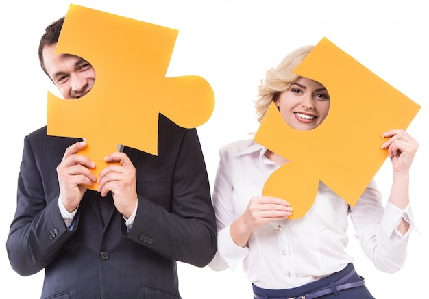 Businessman and woman joining jigsaw pieces of puzzle.