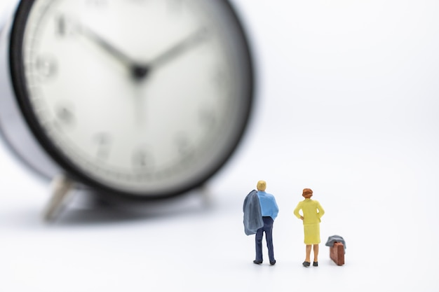 Businessman and woman miniature figure standing and looking to vintage round clock on white.