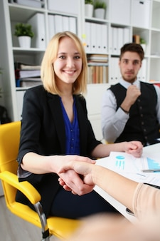 Businessman and woman shake hands as hello