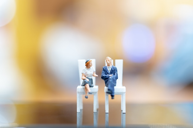 Businessman and woman sitting on chair