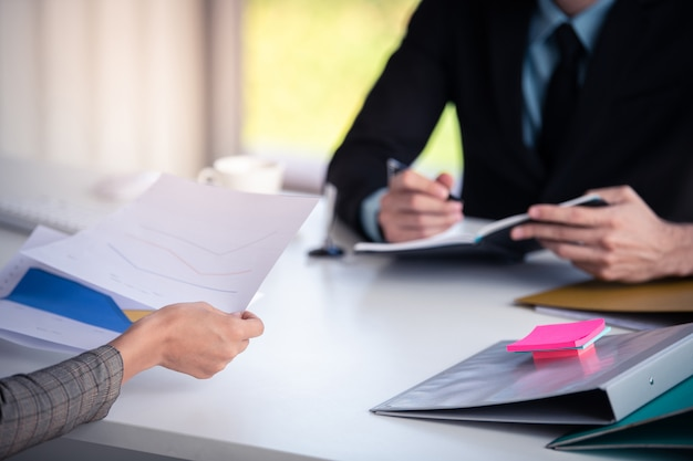 Businessman and woman talking for finance graph  in office