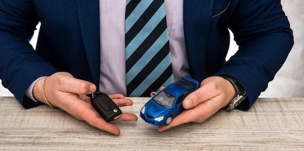 ビジネスマンはオフィスで働く-おもちゃの車と鍵-販売または賃貸自動車のコンセプト