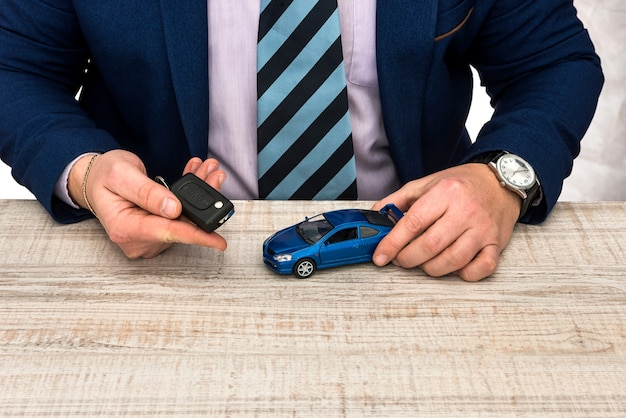 Businessman work at office  toy car and keys  sale or rent auto concept