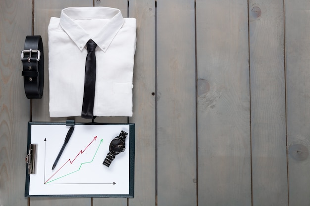 Businessman, work outfit on grey wooden background. white shirt with black tie, belt, planchette. back to work.