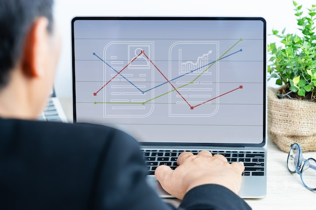 Businessman working analyzing business results in quarter with digital financial report graph layer on laptop computer, showing sales or statistics charts in workplace office. annual reports ideas