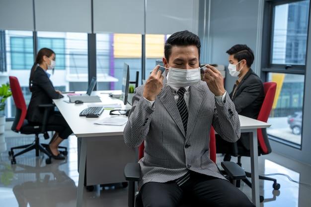 現代のオフィスで働くビジネスマンとcovid-19またはコロナウイルス病を保護するためのマスクを着用してください。