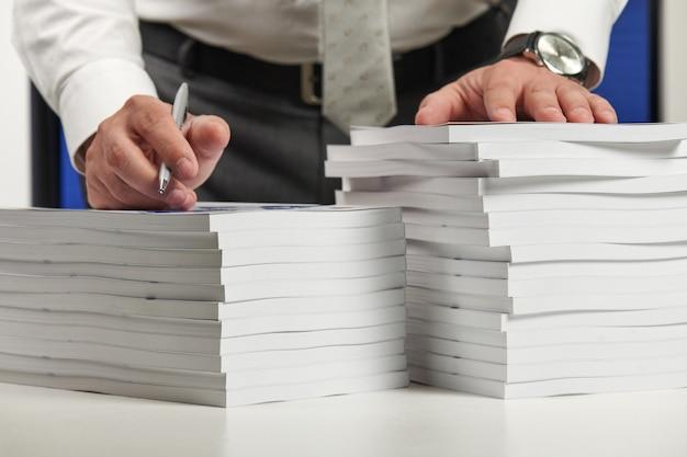 Бизнесмен, работающий в офисе, читает стопку книг и отчетов. концепция финансового учета бизнеса.
